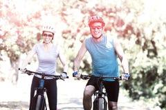 Pares que sonríen y que presentan con sus bicis Fotografía de archivo libre de regalías