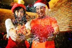 Pares que sostienen el regalo de la Navidad con el fondo del copo de nieve Fotografía de archivo
