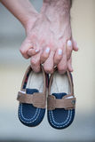 Pares que sostienen las manos y los pequeños zapatos imagen de archivo