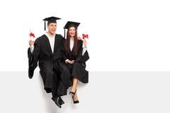 Pares que sostienen los diplomas y que celebran la graduación Imagen de archivo