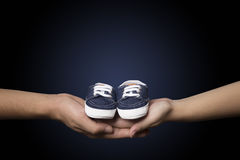 Pares que sostienen los zapatos de bebé azul Fotos de archivo libres de regalías