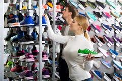 Pares que sostienen pares de zapatos del deporte Fotografía de archivo libre de regalías