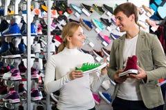 Pares que sostienen pares de zapatos del deporte Imagen de archivo