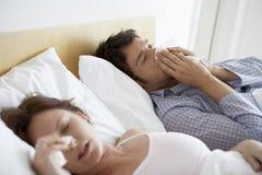 Pares que sufren de fríos en cama Imagenes de archivo