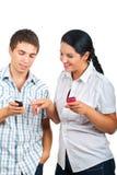 Pares que têm a conversação sobre telefones fotos de stock