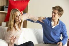 Pares que têm a luta do jogo no sofá Imagens de Stock Royalty Free