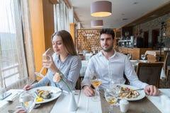 Pares que têm o almoço no restaurante gourmet rústico imagem de stock