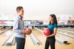 Pares que têm o divertimento com as bolas de boliches na aleia no clube Fotografia de Stock Royalty Free