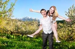 Pares que têm o divertimento em torno das árvores bloomy fotos de stock royalty free
