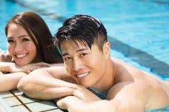 Pares que têm o divertimento na piscina Fotografia de Stock