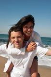 Pares que têm o divertimento na praia Fotografia de Stock