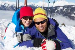 Pares que têm o divertimento no feriado do esqui nas montanhas fotos de stock