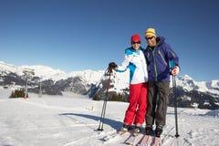 Pares que têm o divertimento no feriado do esqui nas montanhas imagens de stock