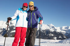 Pares que têm o divertimento no feriado do esqui nas montanhas Imagem de Stock Royalty Free