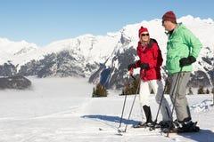 Pares que têm o divertimento no feriado do esqui nas montanhas foto de stock royalty free