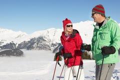 Pares que têm o divertimento no feriado do esqui nas montanhas Fotografia de Stock