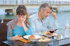 Pares que têm a refeição ambos preocupados com telefones celulares fotos de stock royalty free