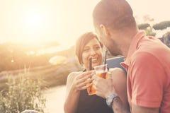 Pares que têm um cocktail exterior no por do sol foto de stock royalty free