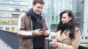 Pares que texting e que falam em seus telefones celulares video estoque