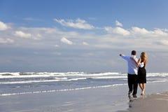 Pares que tienen caminata romántica en una playa Imagen de archivo libre de regalías