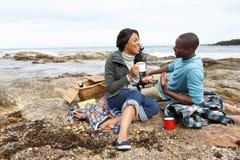 Pares que tienen comida campestre en la playa Fotos de archivo libres de regalías