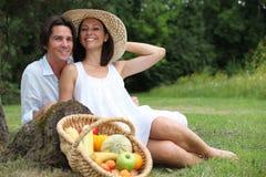 Pares que tienen comida campestre vegetariana. Imagen de archivo libre de regalías