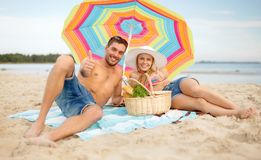 Pares que tienen comida campestre y que toman el sol en la playa Fotografía de archivo