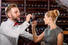 Pares que tienen degustación de vinos romántica en el sótano Imágenes de archivo libres de regalías