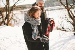 Pares que tienen paseo en parque del invierno cerca del lago congelado Imagenes de archivo