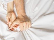 Pares que tienen sexo La mano agarra compresiones una hoja de cama arrugada blanco en una habitación, una muestra del éxtasis, se fotos de archivo