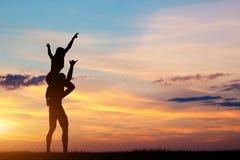 Pares que tienen tiempo feliz junto en la puesta del sol Fotografía de archivo libre de regalías
