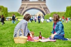 Pares que tienen una comida campestre cerca de la torre Eiffel imágenes de archivo libres de regalías