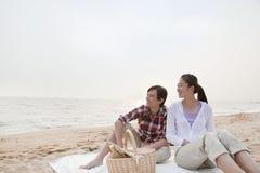 Pares que tienen una comida campestre romántica en la playa Foto de archivo