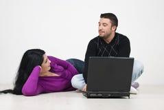Pares que tienen una conversación y que usan la computadora portátil Foto de archivo libre de regalías