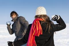 Pares que tienen una lucha de la bola de nieve en invierno Foto de archivo