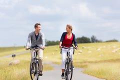 Pares que tienen viaje de la bicicleta de la costa de mar en el dique Imágenes de archivo libres de regalías