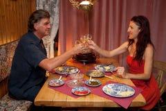 Pares que têm o jantar romântico de Raclette. Foto de Stock Royalty Free