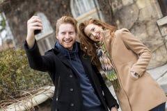 Pares que tomam a foto com telefone celular imagens de stock royalty free