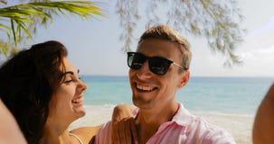 Pares que tomam a foto de Selfie no telefone esperto da pilha no beijo da praia, no homem de sorriso feliz e na mulher Toursits n video estoque