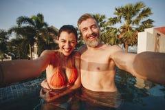 Pares que tomam imagens em uma piscina foto de stock