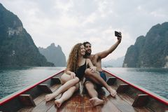 Pares que tomam o selfie em um barco do longtail foto de stock