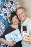 Pares que toman el autorretrato con el teléfono celular en Front Of Christmas Tree Fotografía de archivo libre de regalías