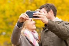Pares que toman el selfie con smartphone en parque Foto de archivo