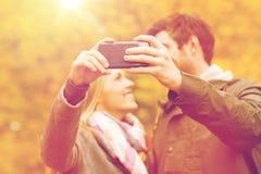 Pares que toman el selfie con smartphone en parque Fotos de archivo libres de regalías