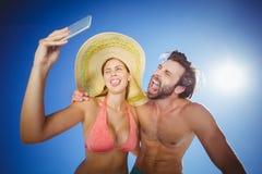 Pares que toman el selfie contra el cielo azul Imagen de archivo libre de regalías