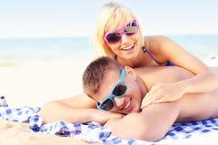 Pares que toman el sol en la playa Imagenes de archivo