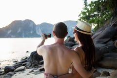 Pares que toman imágenes en la playa fotografía de archivo
