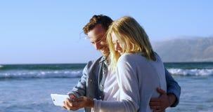 Pares que toman Selfie en el teléfono móvil en la playa almacen de metraje de vídeo