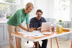 Pares que trabalham junto na mesa no escritório domiciliário fotos de stock