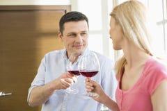 Pares que tuestan las copas de vino rojas en cocina Imagen de archivo libre de regalías